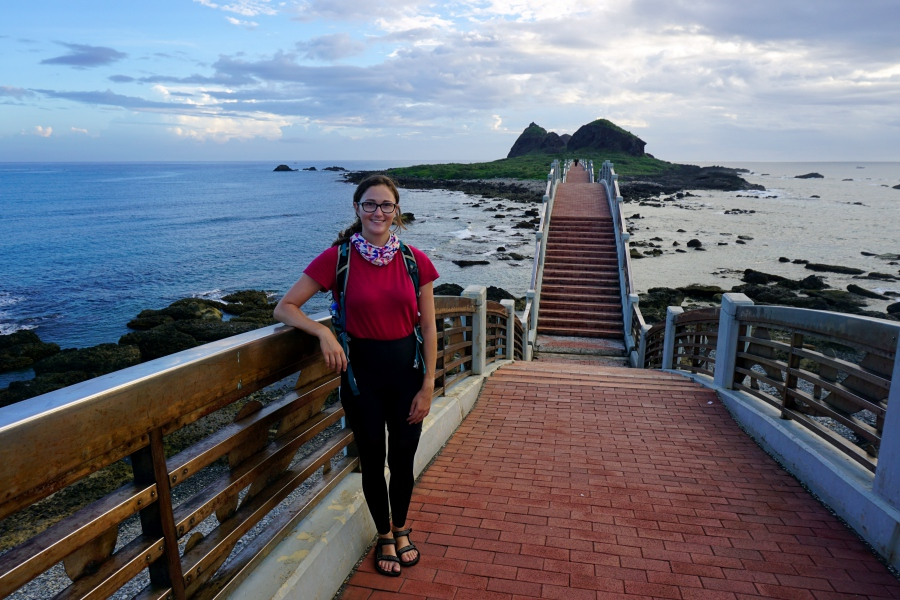 Tourist standing on the Sanxiantai Arch Bridge in Taiwan (ocean in the background)