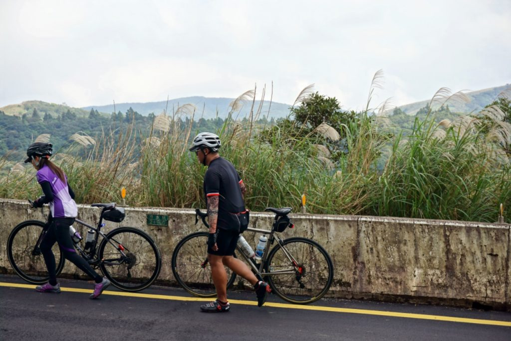 Two Taiwanese pushing their roadbikes up a hill